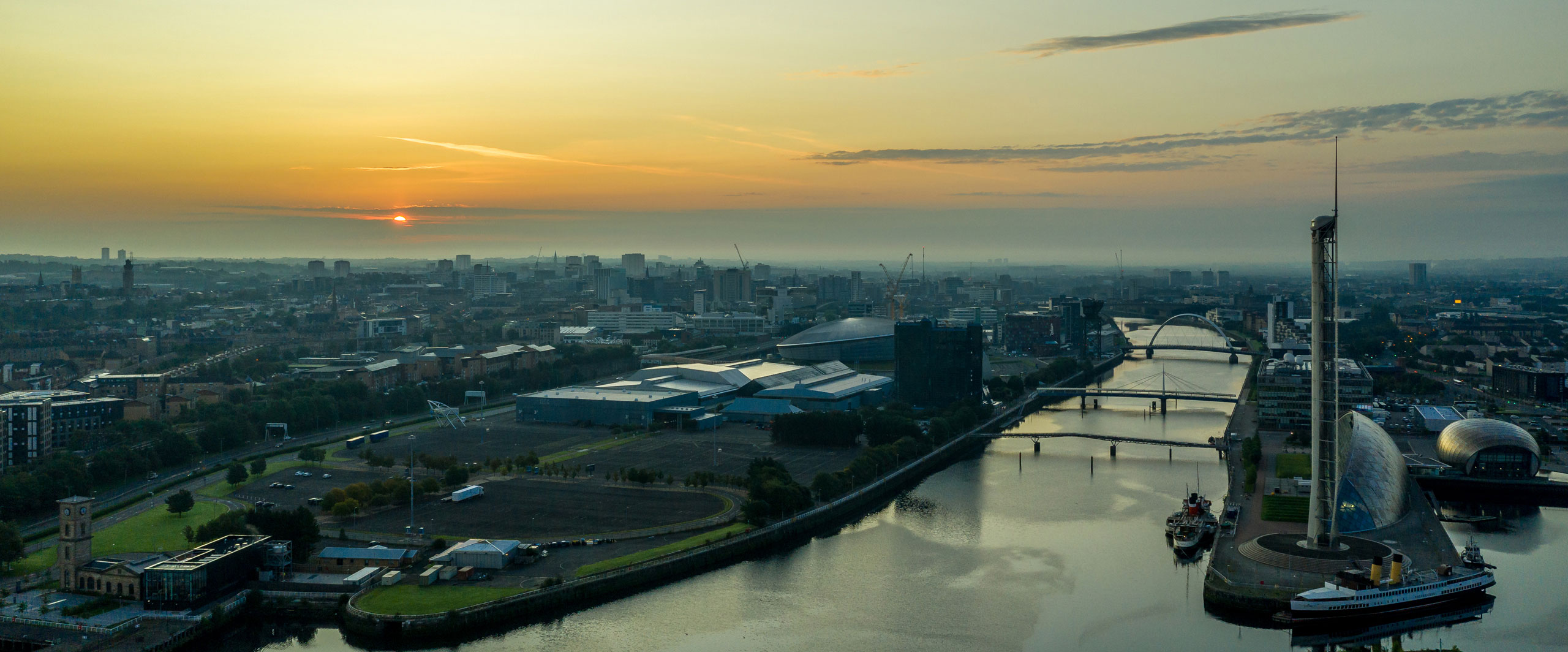 Dawn over the city of Glasgow, Scotland, with River Clyde - Attribution: Ian Dick - Licence: CC 2.0 - https://creativecommons.org/licenses/by/2.0/deed.en - Source: https://commons.wikimedia.org/wiki/File:Dawn_over_Glasgow_(48659596342).jpg
